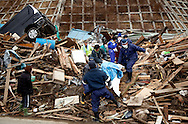 Japanese forces working in the town of Rikuzen Takada find a dead body after the earthquake and tsunami hit the town on 11 March 2011.