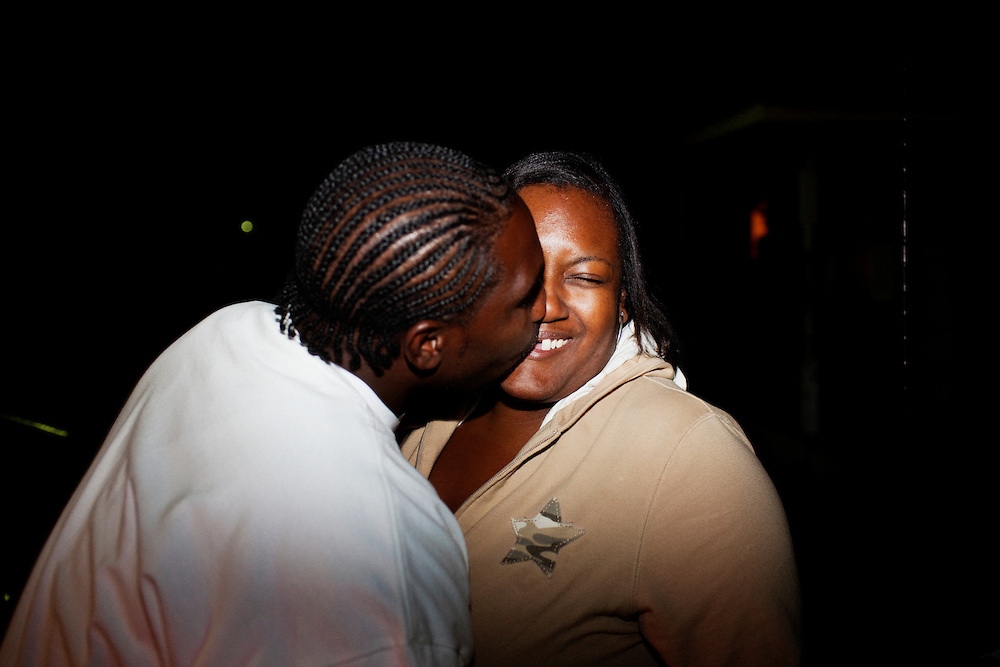 """""""Tee"""" horses around with a woman, kissing her in the night after a funeral for Demetrius """"Butta"""" Anderson in the  Baptist Town neighborhood of Greenwood, Mississippi on Friday, November 5, 2010. Butta was murdered the week before."""