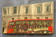 A bus reflected in brass the sign to number 1 Parliament street, Westminster, London.