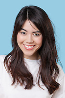 Portrait of smiling mixed race young woman over blue background