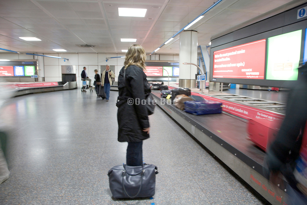 airplane passenger waiting for her luggage