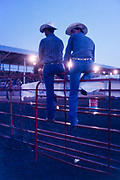 Two cowboys sitting on the perimeter fence of a rodeo arena during the county fair in Meredosia, Illinois