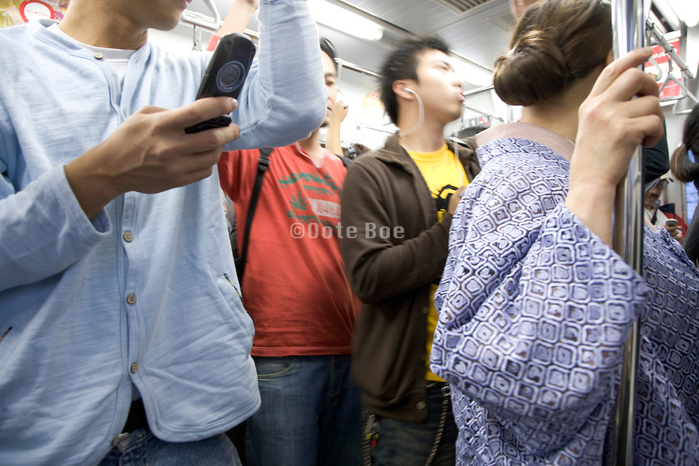 young Japanese man text messaging while traveling on the train Tokyo Japan