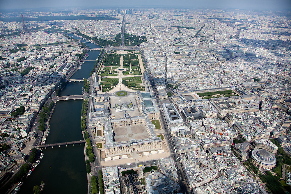Looking above the Louvre Museum down the Jardin de Tuileries (a public garden located between the Louvre Museum and the Place de la Concorde) and the Champs-Elysees with the Eiffel Tower in the background and the Seine river running along the left bank.