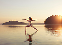 Young woman practicing Hatha yoga on a floating platform in water on the lake during sunrise in the morning. Yoga Warrior posture, Veerabhadrasana. Muskoka, Ontario, Canada.