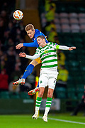Marcel Halstenberg (#23) of RB Leipzig outjumps Mikael Lustig (#23) of Celtic FC during the Europa League group stage match between Celtic and RP Leipzig at Celtic Park, Glasgow, Scotland on 8 November 2018.