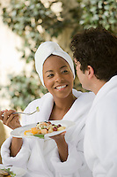 Couple in bathrobes, eating at health spa