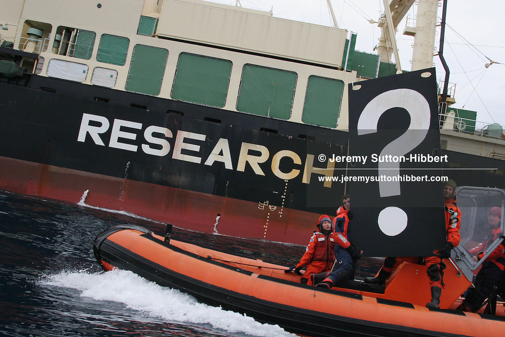 """Greenpeace activists hold a banner beside the Nisshin Maru """"Research"""" factory ship, questioning its """"research"""" methods. Southern Ocean, 12.01.2006"""