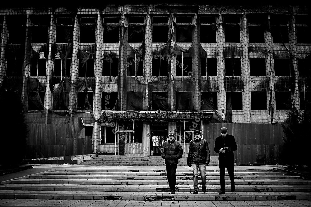Three men are walking in front of the destroyed City Hall in Dzerzhynsk, near the frontline in eastern Ukraine.