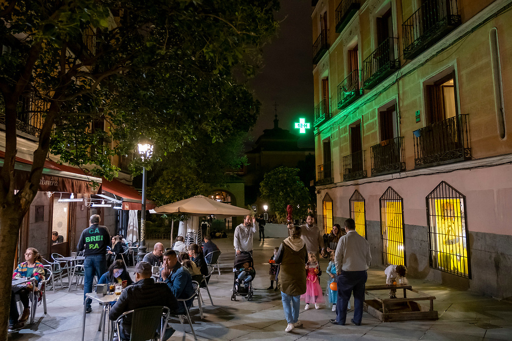 People sitting outside eating dinner and having drinks at a bar on the Plaza del Dos de Mayo next to the green cross sign of a pharmacy on the 31st of October 2019 in Madrid, Spain.  (photo by Andrew Aitchison / In pictures via Getty Images)