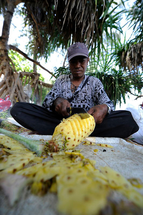 Man cutting pineapple in Thailand