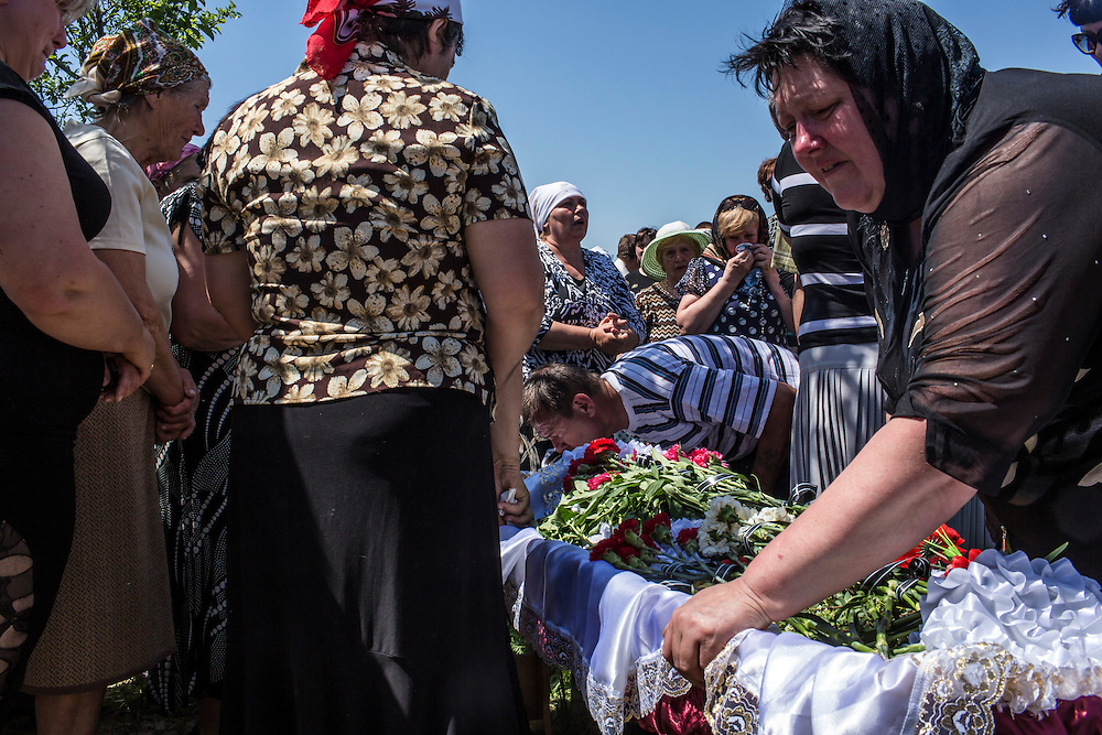 STAROVARVAROVKA, UKRAINE - MAY 16:  Mourners attend the burial of Elena Ott, 42, is carried out of her family's house on May 16, 2014 in Starovarvarovka, Ukraine. Ott was killed two days prior when the car she was riding in was fired on by forces her family believes to be the Ukrainian military. (Photo by Brendan Hoffman/Getty Images) *** Local Caption ***