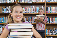 Two school children with books in library, portrait