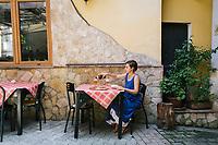 NAPLES, ITALY - 1 AUGUST 2018: A customer has lunch at Cantina del Gallo, a family-owned restaurant in the Rione Sanità in Naples, Italy, on August 1st 2018.<br /> <br /> Cantina del Gallo, in the Rione Sanità, was established in 1898 and run by four generations of the Silvestri family. The cantina began as a store selling bulk wine and oil. It was only in the 1950s, when the legendary Aunt Cuncetta began cooking, that it became the simple and genuine tavern it is today.<br /> There are three dishes that are the restaurant's workhorses, and the ones we always seem to rotate between: the pennette alla sorrentina (a variation of the classic gnocchi alla sorrentina, seasoned with tomato, basil and stringy mozzarella), the baked cod (although the fried cod is just as mouth-watering) and the pizza cafona (peasant pizza), topped with oregano, cheese, chile and with double the tomatoes (tomato juice and chopped tomatoes).