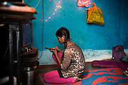 Poonam, 12, is turning on the old television inside her family's newly built home in Oriya Basti, one of the water-contaminated colonies in Bhopal, central India, near the abandoned Union Carbide (now DOW Chemical) industrial complex, site of the infamous '1984 Gas Disaster'.