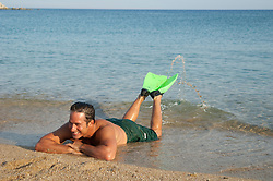 good looking man enjoying his vacation in Greece by relaxing in the sea with flippers on his feet
