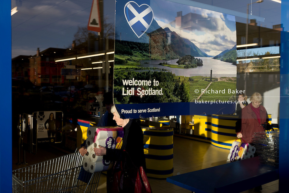 Shoppers inside a Glasgow branch of supermarket chain Lidl with corporate colrs and checkout counter and welcome to Scotland poster