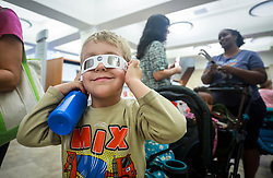 August 15, 2017 - West Palm Beach, Florida, U.S. - JONATHAN GALASSINI, 4, of West Palm Beach, tries on a pair of solar eclipse glasses at Mandel Public Library in West Palm Beach Tuesday. The library was giving out free verified solar eclipse glasses to library cardholders. (Credit Image: © Bruce R. Bennett/The Palm Beach Post via ZUMA Wire)