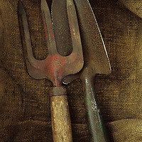 Close up from above of well-used garden trowel and hand fork lying on hessian sack