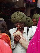 Men in green turbans wallking through crowd, Pushkar, Rajasthan.