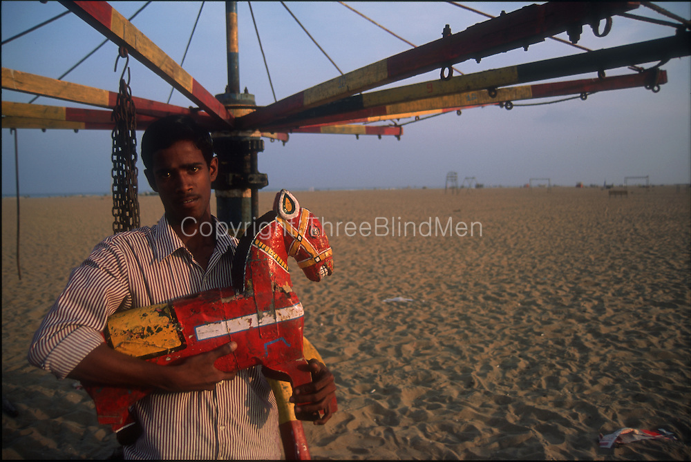 India.  On Marina beach, a man sets up his merry-go-round for the evning crowd.<br />