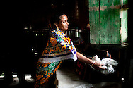 Shahida Begum, 35, cleans her product bag as she goes about her daily household chores in her hut in Palashbari Villlage, Taragonj, Rangpur, Bangladesh on 18th September 2011, after a regular day of work as a saleswoman earning 3500 - 5000 Bangladeshi Taka per month. She is one of many rural Bangladeshi women trained by NGO CARE Bangladesh as part of their project on empowering women in this traditionally patriarchal society. Named 'Aparajitas', which means 'women who never accept defeat', these women are trained to sell products in their villages and others around them from door-to-door, bringing global products from brands such as BATA, Unilever and GDFL to the most remote of villages, and bringing social and financial empowerment to themselves.  Photo by Suzanne Lee for The Guardian
