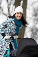 Mother walking with baby carriage in park (portrait)