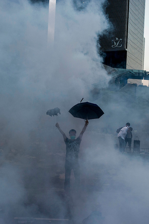 A protestor defies riot police surrounded by tear gas during the riots that followed the demonstrations as protest for the arrest of students who entered the headquarters of the Legislative Counsel on 28 September 2014 in Hong Kong. More than 50,000 faced police after occupying the highway as as part of the pro-democracy demonstration in the former British colony. AFP PHOTO / XAUME OLLEROS