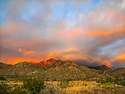 The setting sun reflects on the Sandia Mountain peak.