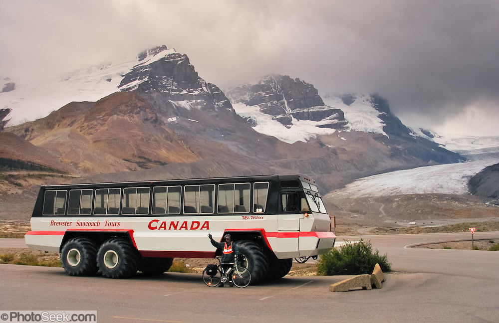A glacier bus dwarfs a bicyle at Columbia Icefield Visitor Center in Jasper National Park, along a 187-mile bicycle ride from Jasper to Banff in Alberta, CANADA. Brewster Snocoach Tours buses drive tourists onto Athabasca Glacier. This is part of the Canadian Rocky Mountain Parks World Heritage Site declared by UNESCO in 1984.