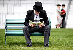A racegoer looks through a Royal Ascot pamphlet during day two of Royal Ascot at Ascot Racecourse.