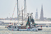 A decorated shrimp boat parades down the Cooper River past the city skyline during the annual Blessing of the Fleet signifying the start of the commercial shrimping season April 30, 2017 in Charleston, South Carolina. Coastal shrimping is part of the low country heritage but has been declining rapidly with rising costs and increased foreign competition.