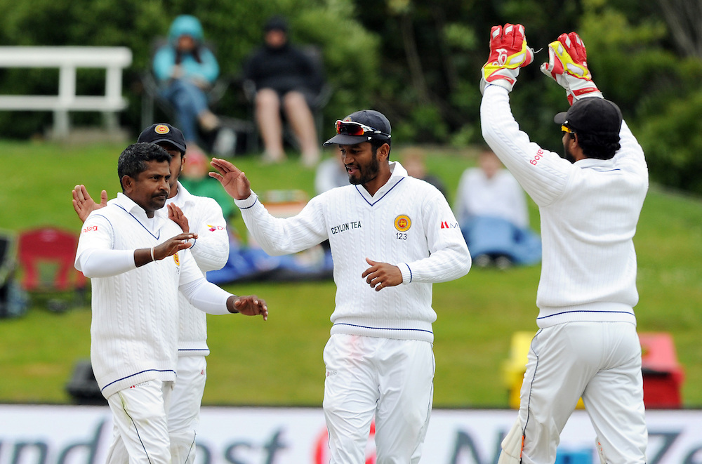 Sri Lanka's Rangara Herath, left, after taking the wicket of New Zealand's Martin Guptill for 46 on day three of the first International Cricket Test, University Cricket Oval, Dunedin, New Zealand, Saturday, December 12, 2015. Credit:SNPA / Ross Setford