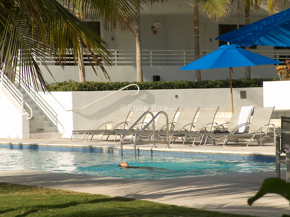 woman alone swimming in the pool of a luxury hotel Miami Beach USA