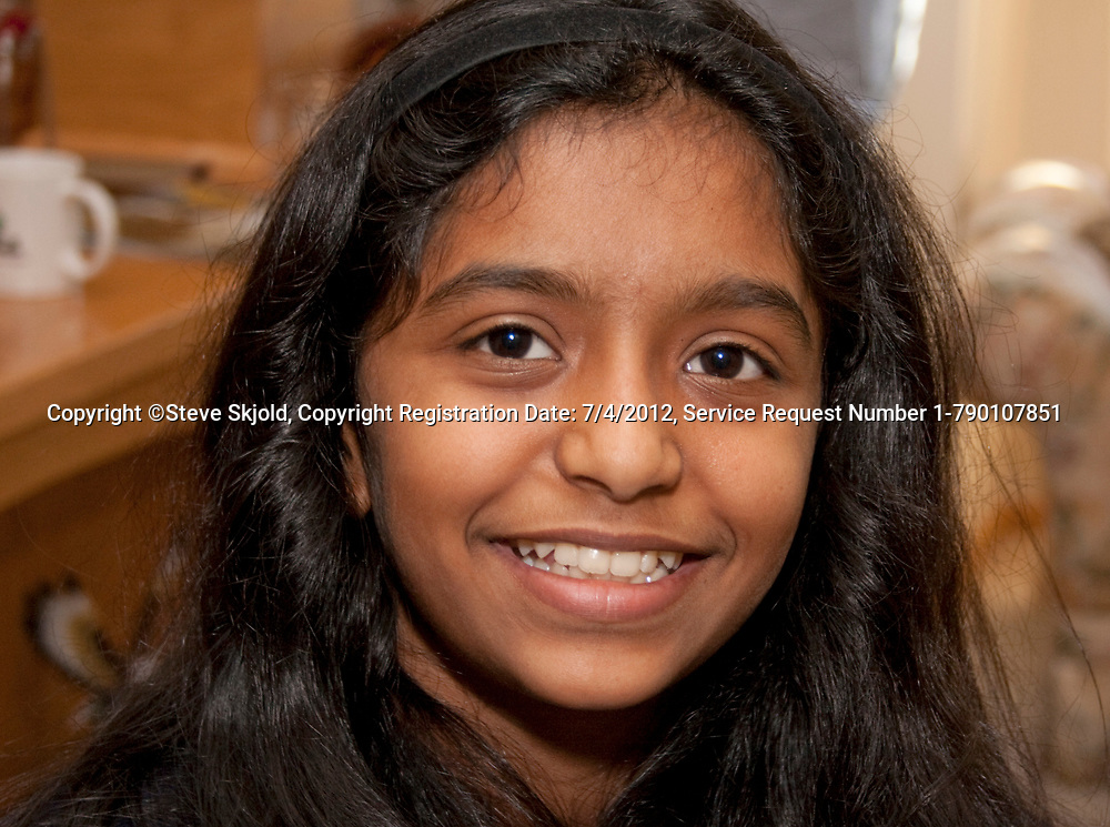 Happy girl age 11 of East Indian heritage celebrating Thanksgiving holiday in her relatives home. Champlin Minnesota MN USA