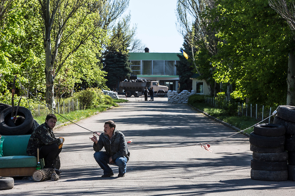 KRAMATORSK, UKRAINE - APRIL 25:  Pro-Russian separatists guard a barricade controlling access to the civilian air field on April 25, 2014 in Kramatorsk, Ukraine. Earlier in the day, a Ukrainian military helicopter was destroyed at the military portion of the air field, with separatists claiming they had shot the helicopter down. (Photo by Brendan Hoffman/Getty Images) *** Local Caption ***