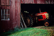 Old red tractor sticking out of a old red barn on the country farm in rural America