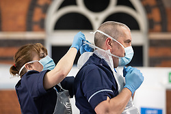 © Licensed to London News Pictures. 13/04/2020. Manchester, UK. Nursing staff on Ward 7 put on their PPE ahead of the hospital's official opening on Friday 17th April 2020 . The National Health Service has built a 648 bed field hospital for the treatment of Covid-19 patients , at the historical railway station terminus which now forms the main hall of the Manchester Central Convention Centre . The facility is due to open this week (commencing Easter Monday , 13th April 2020 ) and will treat patients from across the North West of England , providing them with general medical care and oxygen therapy after discharge from Intensive Care Units . Photo credit: Joel Goodman/LNP