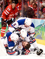The Ducks' Corey Perry, rear, can only watch as a helmetless Ryan Kesler, is mobbed by teammates after scoring an empty net goal to seal the U.S.'s 5-3 victory over Team Canada Sunday at the 2010 Olympic Winter Games in Vancouver, BC.