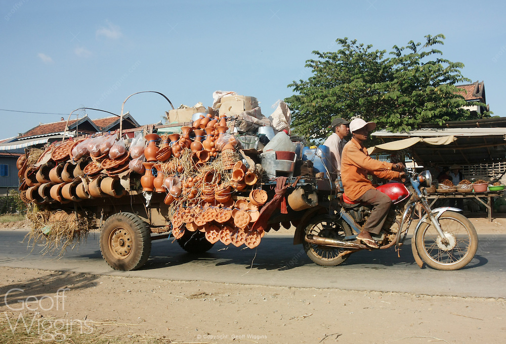 Motorbike market with overloaded cart, on country road, Cambodia