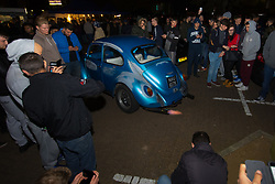 London, April 16th 2017. Hundreds of car enthusiasts gather with their souped up vehicles for the '2017 Tunnel Run', an where they take to the streets of London for a high speed 'cruise' through several of its tunnels and over bridges, cruising past famous landmarks. With complaints from some members of the public over noise and road safety grounds, police keep an eye on the drivers with the threat of siezing cars from unruly drivers. The event begins with a static meet-up at Canada Water before the cars set off on their cruise through the streets of the capital. PICTURED: A VW beetle spits flames from its exhaust.<br /> <br /> Credit: &copy;Paul Davey