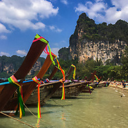 Majestic limestone cliffs serve as a scenic backdrop for tourists roaming the beach and the many longtail boats anchored at West Railay Beach, Krabi, Thailand.