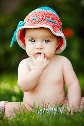 Baby Girl Wearing Knitted Hat Sitting on Grass