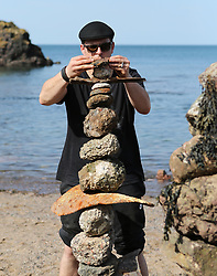 European Stone Stacking 2019 21 April 2019; A competitor puts the finishing touches to his sculpture during the European Stone Stacking 2019 at Eye Cave Beach, Dunbar.<br /> <br /> (c) Chris McCluskie | Edinburgh Elite media