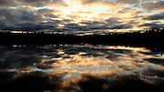 The setting sun, struggling to reach the surface of Gibson Lake through the remnants of of an afternoon rain cloud, creates a most unique reflection on the surface.