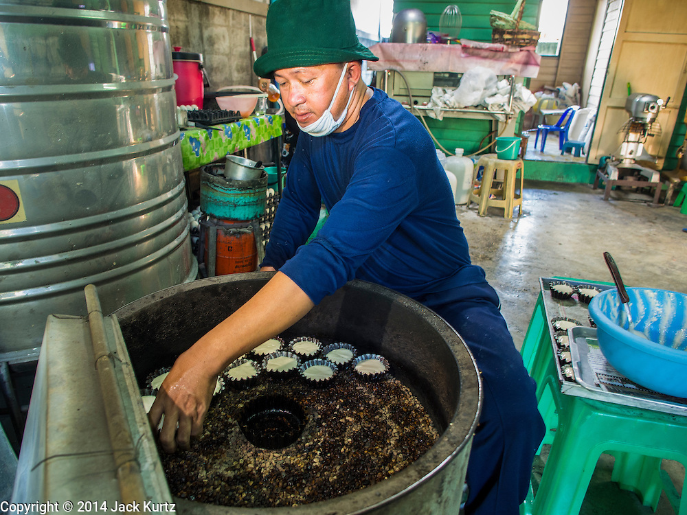 """28 OCTOBER 2014 - BANGKOK, THAILAND:  A worker puts cakes into the traditional oven at the Pajonglak Maneeprasit Bakery in Bangkok. The cakes are called """"Kanom Farang Kudeejeen"""" or """"Chinese Monk Candy."""" The tradition of baking the cakes, about the size of a cupcake or muffin, started in Siam (now Thailand) in the 17th century AD when Portuguese Catholic priests accompanied Portuguese soldiers who assisted the Siamese in their wars with Burma. Several hundred Siamese (Thai) Buddhists converted to Catholicism and started baking the cakes. When the Siamese Empire in Ayutthaya was sacked by the Burmese the Portuguese and Thai Catholics fled to Thonburi, in what is now Bangkok. The Portuguese established a Catholic church near the new Siamese capital. Now just three families bake the cakes, using a recipe that is 400 years old and contains eggs, wheat flour, sugar, water and raisins. The same family has been baking the cakes at the Pajonglak Maneeprasit Bakery, near Santa Cruz Church, for more than 245 years. There are still a large number of Thai Catholics living in the neighborhood around the church.  PHOTO BY JACK KURTZ"""