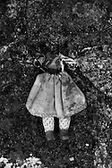 """A headless doll left at a garden. Childhood must not be a period of crisis. In Portugal , as in generally the  """"occidental world"""", the public debt extends to future generations, forming a depressing future where insecurity reigns. The austerity policies affect human evolution in its most basic principles. What is the future? Children are the future, the hope for a better world depends on education in its broadest sense. Money from taxes are not invested in education or health, are used to support the debt and the banking system. In this project I focused on a fragment of a more general work about the crisis, alluding childhood and its consequences in the current socio-economic context."""