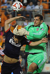 Houston goalkeeper Tally Hall, right, makes a save over New England's Kelyn Rowe, center, as Houston's Brad Davis defends during the first half of a MLS soccer game, Saturday, March 8, 2014, at BBVA Compass Stadium in Houston. (Photo: Eric Christian Smith/For the Chronicle)