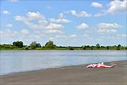 Nederland, Wijhe, 4-6-2015Een jonge vrouw ligt alleen te zonnen aan de oever van de IJssel . Ze ligt op de verharde kadeFoto: Flip Franssen