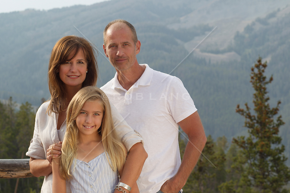 portrait of a woman, man and young girl posing for a family portrait overlooking a mountain range in Montana